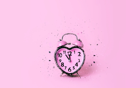 Heart shaped clock on pink background. Valentines day and love and duration concept. Stock Photo