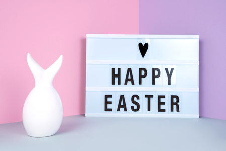 Creative easter composition with easter bunny on pink and lilac background. Stock Photo