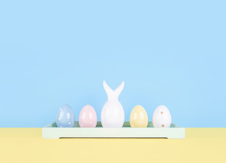 Creative easter composition with painted eggs and easter bunny on yellow and blue background.