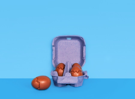 Easter composition with chocolate eggs on blue background with space for text.
