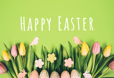 Creative easter composition with painted eggs against green background.