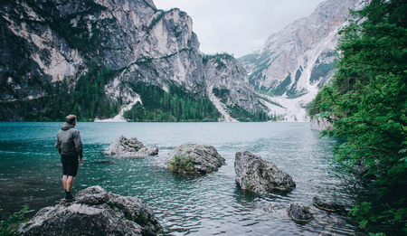 Hiker enjoing beautiful view of Lago di Braies or Pragser wildsee, Trentino Alto Adidge, Dolomites mountains, Italy.