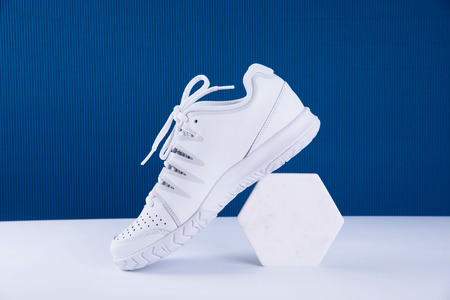 Pair of white sneakers on blue background. Healthy lifestyle concept.