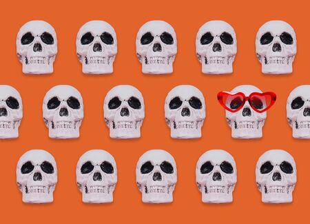 Skull pattern on orange background. Creative Halloween concept.