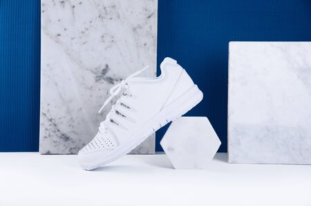 Pair of white sneakers on trendy blue background. Healthy lifestyle concept.