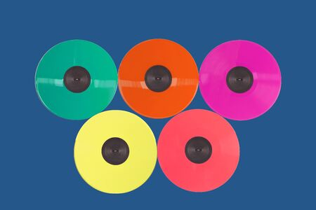 Colored vinyl records collection on a blue background. Trendy color.