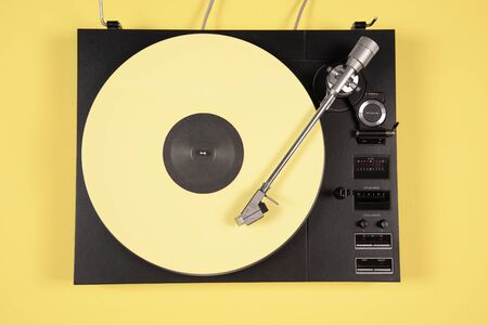 Colored vinyl record on a yellow background with copy space. Top view. Stok Fotoğraf