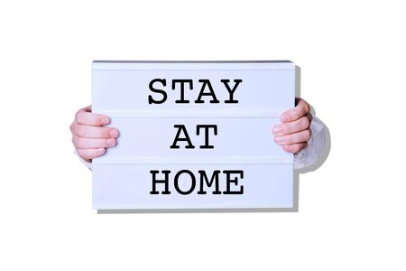 Male hands with Stay At Home sign on white background. Minimal art style. Stok Fotoğraf
