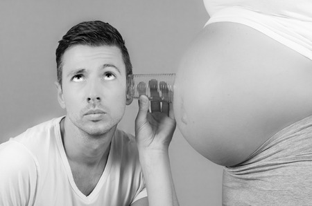 funny father listening with a glass on the belly of his pregnant wife in black and white Stock Photo