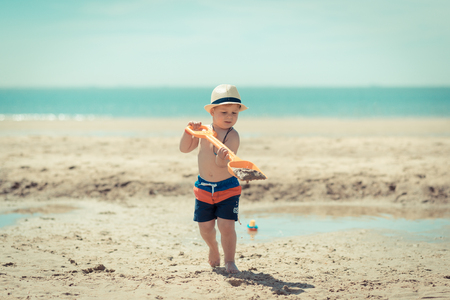 Little boy child walking at the camera with a shovel in his hands on the beach