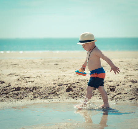 boy is running on the beach with his hat on