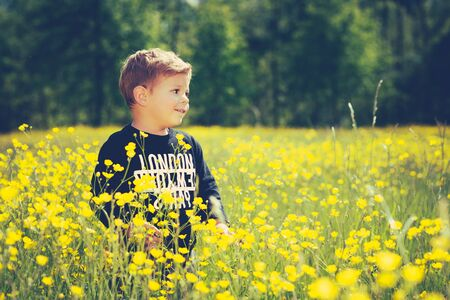 little cute boy child in a wonderful field of yellow flowers smiling and laughing
