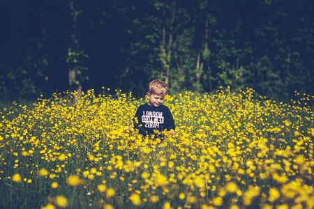 naturally: little cute boy child in a wonderful field of yellow flowers smiling and laughing