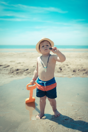 amazing kid looking at a shell on the beach