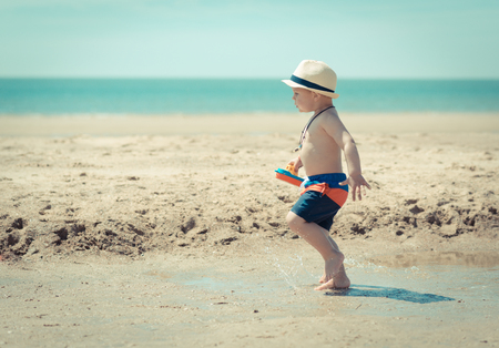 little kid is running in the sand on the beach with a toy boat in his hands