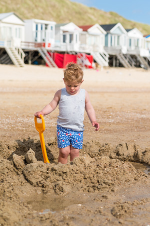 boy on the beach with a shovel in the sand