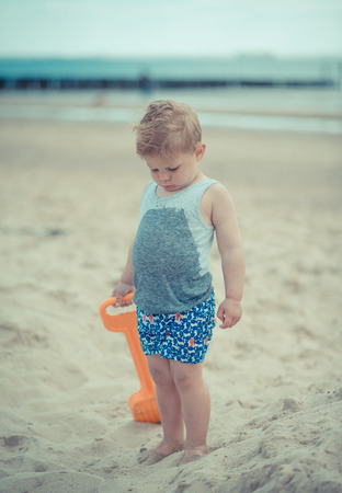 upset boy child on the beach with a wet shirt Stock Photo