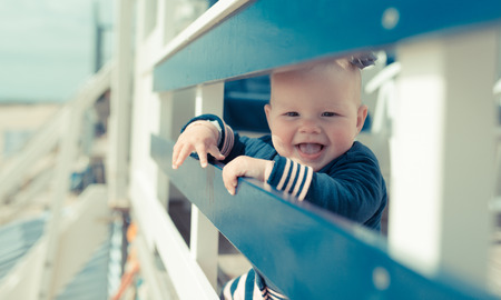 cute little baby girl on the beach house laughing and smiling Stock Photo