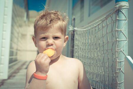 Little boy eating an icecream at the beach house