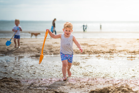 boy child running on the beach with a shovel in his hands