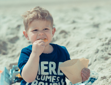 fat boy child on the beach eating salty snacks 스톡 콘텐츠
