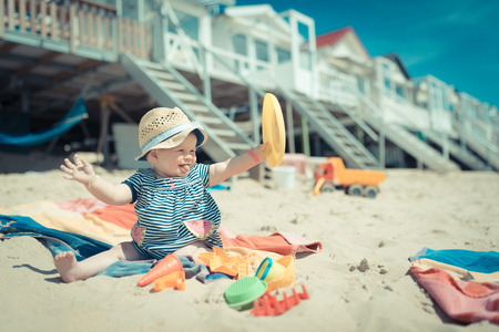 baby girl sitting in a sand on the beach playing and laughing