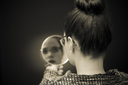 mirror face: ego businesswoman looking in the mirror and reflecting Stock Photo