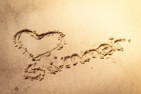 handwritten textin the sand on the beach during the summer holidays