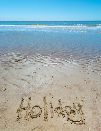 text in the sand on the beach during the summer holidays Stock Photo