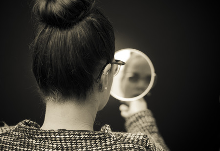 black and white image: ego businesswoman looking in the mirror and reflecting Stock Photo