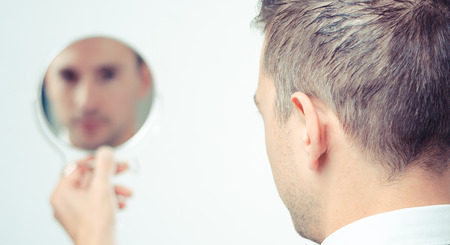 on mirrors: Ego business man looking in the mirror and reflecting