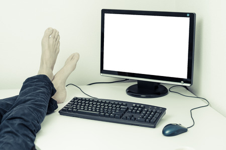relaxing feet next to the computer with white screen