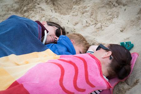 Family sleeping on the beach