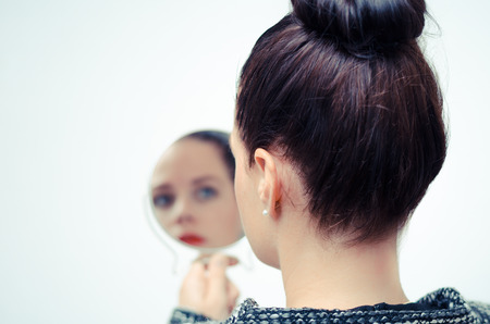 on mirrors: ego businesswoman looking in the mirror and reflecting Stock Photo