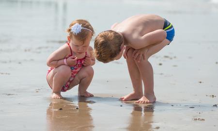 niñas jugando: el descubrimiento y la exploración de la playa Foto de archivo