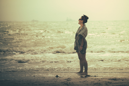 shes wearing a dress and shes looking and thinking at the sea