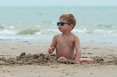 the kid is sitting in the sand looking around