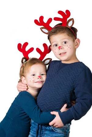 lovely and adorable brother and sister family portrait in christmas style reindeers