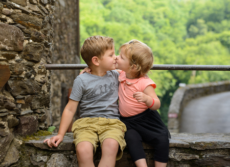Lovely and adorable brother and sister girl giving each other a kiss, family love Stock fotó