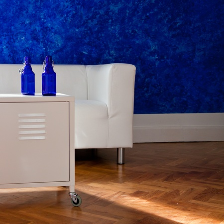 White table, with blue bottles, and whitecouch against blue wall