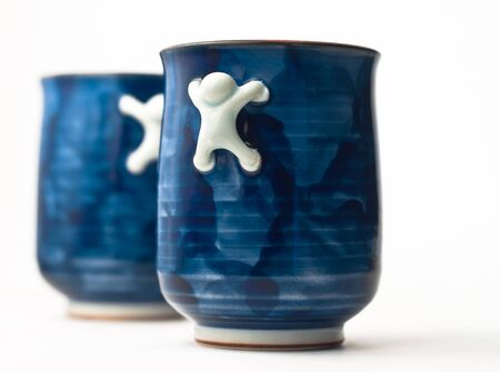 Two blue cups with crawling men as handles