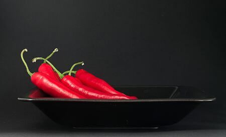 Bunch of chillies on a black plate photo