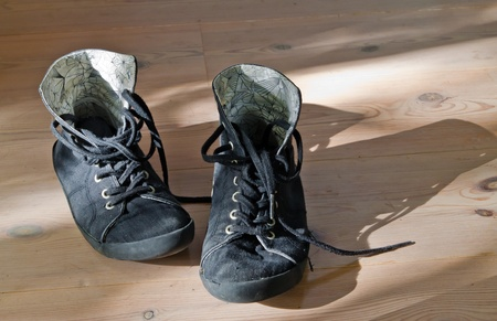 Old black worn out sneakers on wooden floor Stock Photo