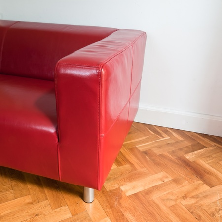 Red sofa in a room with oak parquet fllor and white walls