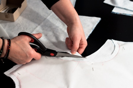 sewing pattern: Designer cutting fabric with a taylors scissors Stock Photo