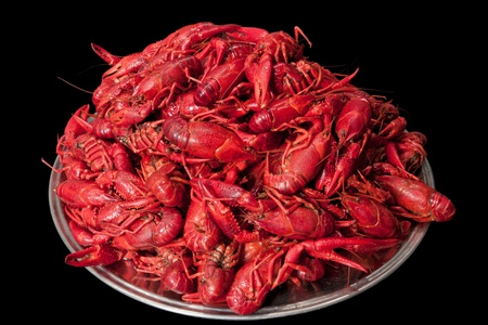 A plate with many red cooked crayfish stacked in a pile. Isolated on black background photo
