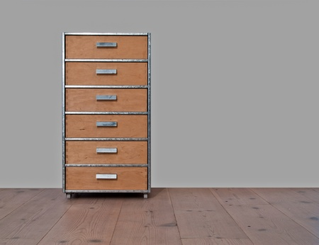 Chest of drawers of wood and metal, standing on a wooden plank floor