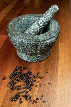 Stone mortar on a hard wood surface with peppercorns photo