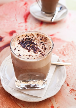 Two glasses of caffe latte on a red pattern table photo