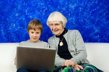 Grandmother and grandchild sitting in a sofa looking at a laptop photo